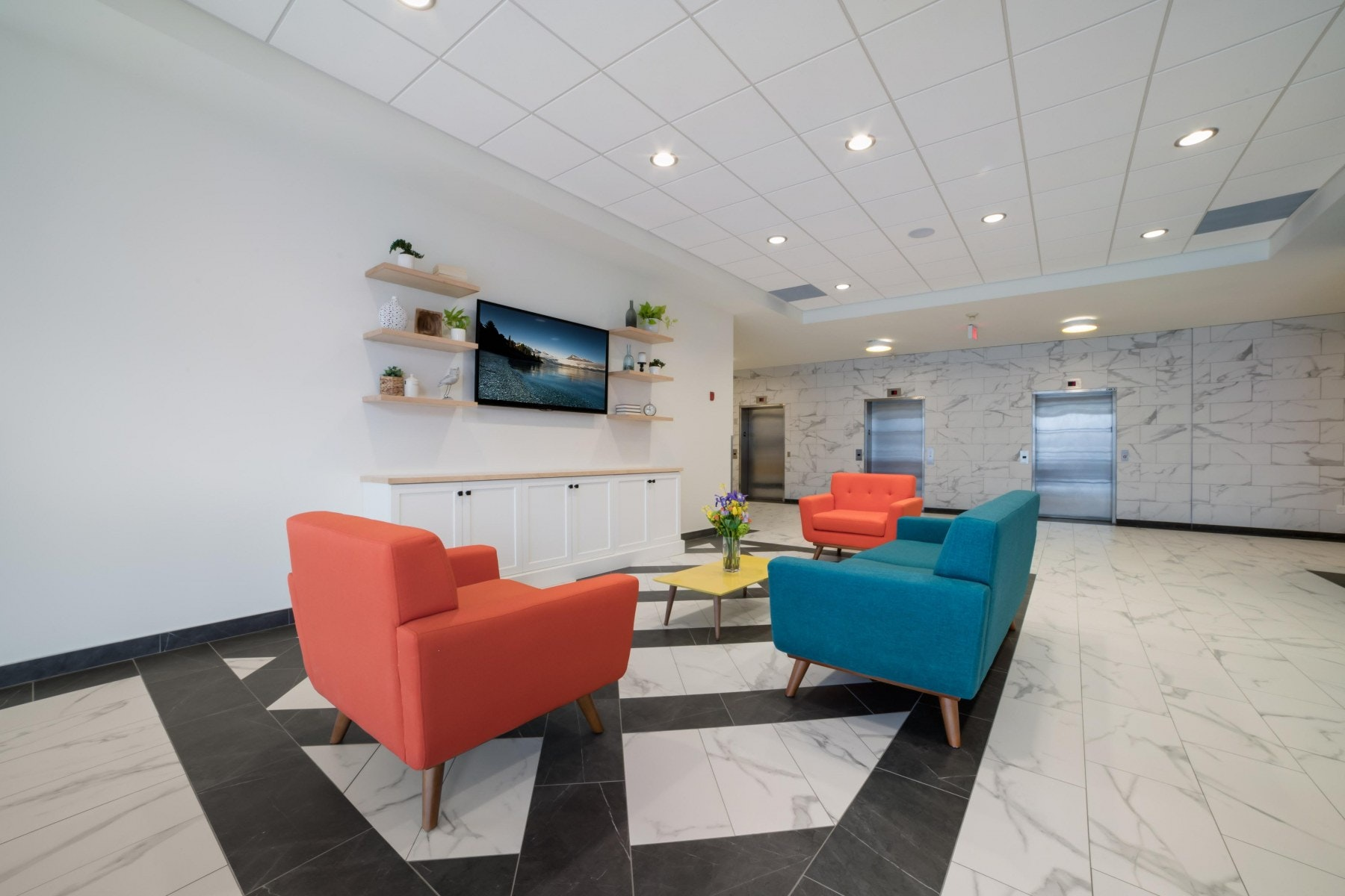 Lobby with couches, TV and shelves