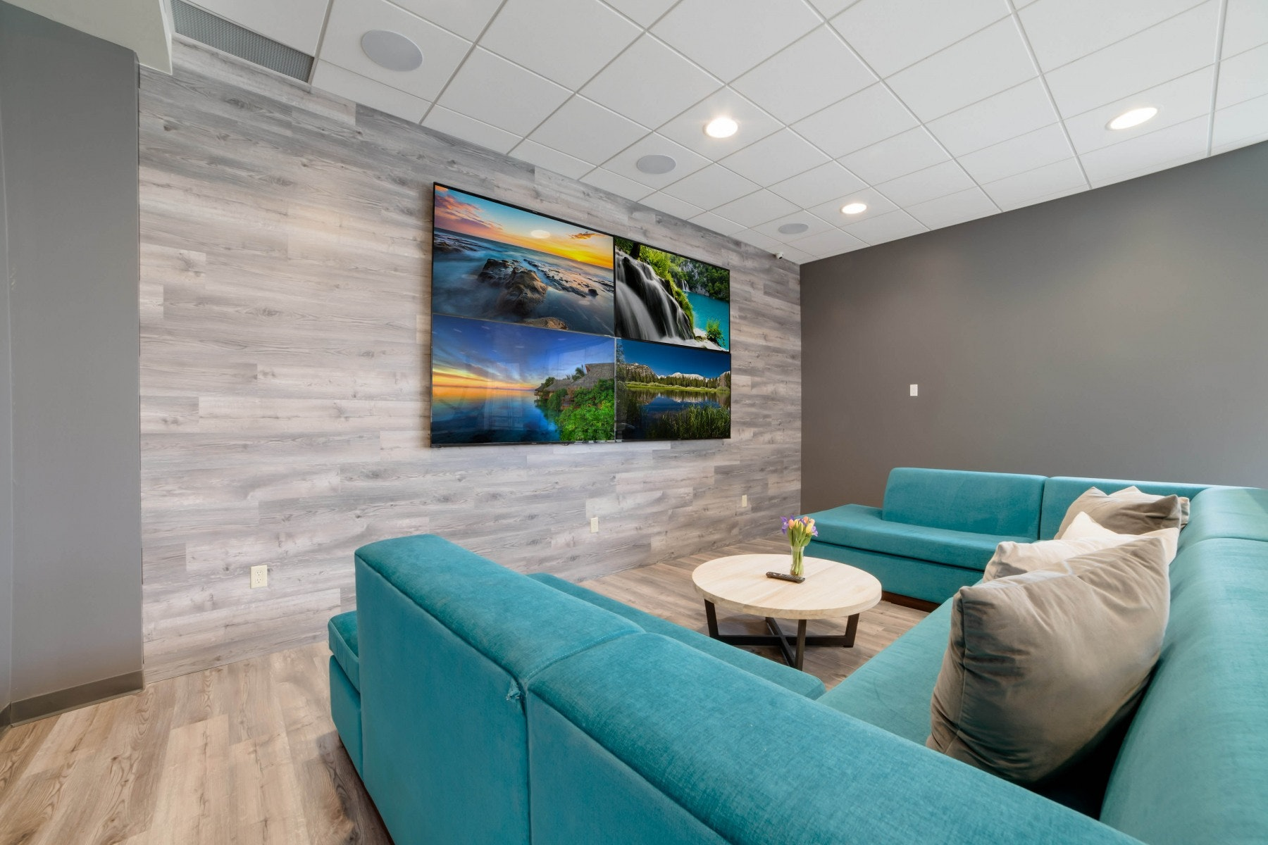 Big screen TV with blue couch and coffee table