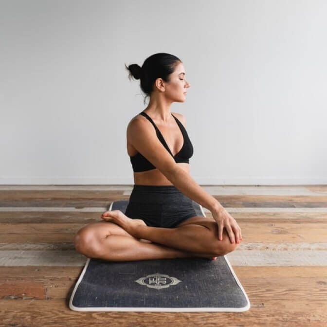 a woman sitting with her legs crossed doing yoga