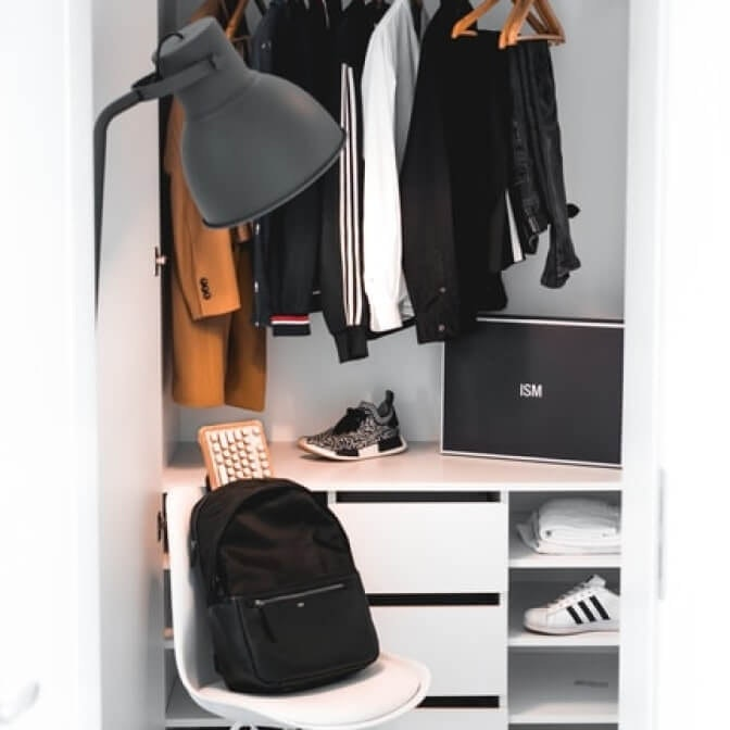 a closet with clothes and shoes, a backpack on a chair