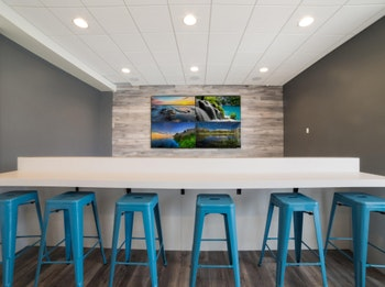 games room seating with blue stools and 4k tv