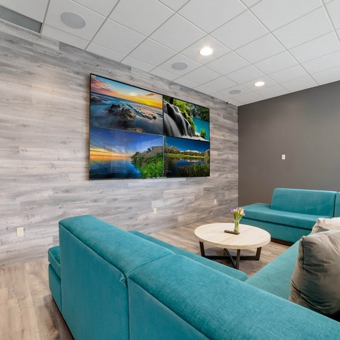 space with blue couches, a center table, and a large 4k TV