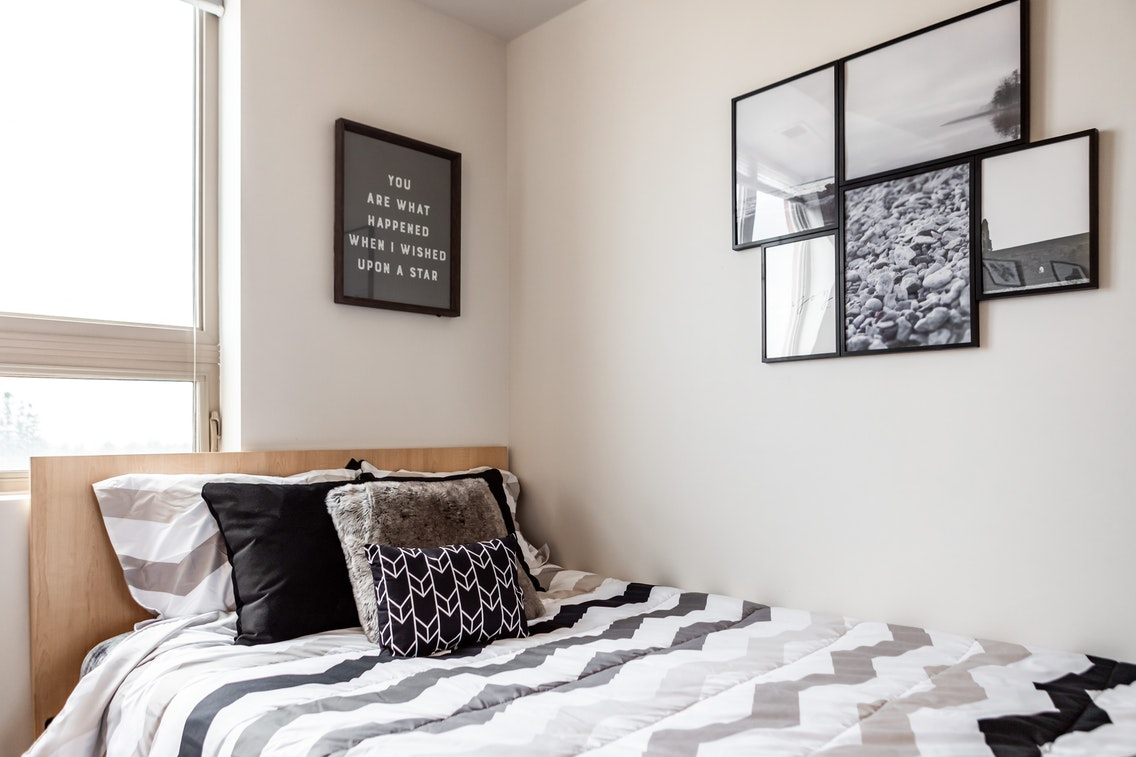 Single bed with two pictures on the wall